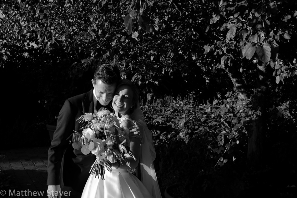 A black and white candid photograph of the bride and groom moments after their ceremony.